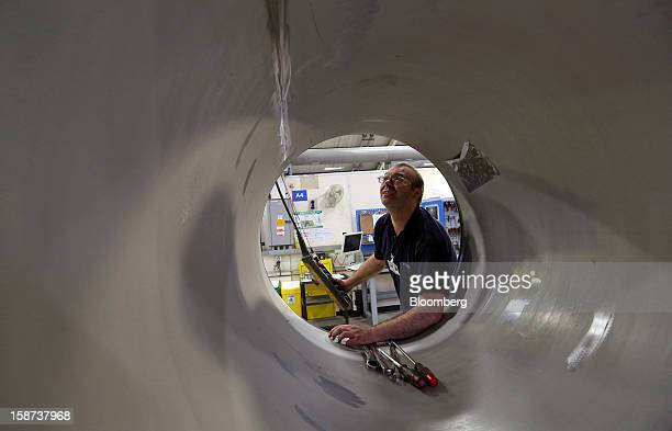 An employee inspects the steel vessel of a magnet to be used in Magnetic Resonance Imaging scanners during manufacture at the Siemens AG Magnet...