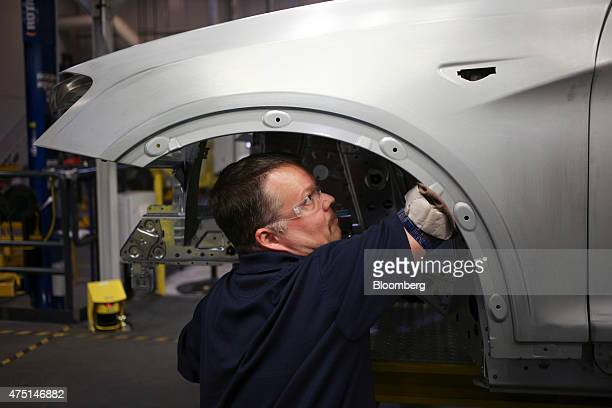 An employee inspects the wheel well of a Bayerische Motoren Werke AG X4 sports utility vehicle on the assembly line at the BMW Manufacturing Co...