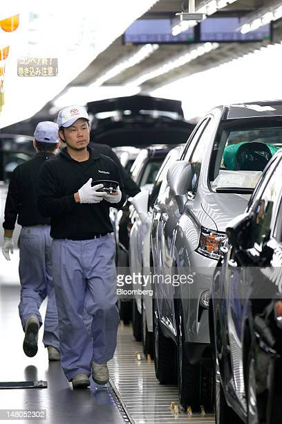 An employee inspects Toyota Motor Corp Lexus vehicles on the production line of Toyota Motor Kyushu Inc's Miyata plant in Miyawaka City Fukuoka...