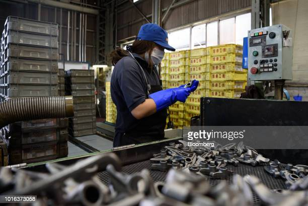 An employee inspects vehicle parts at an Asahi Tekko Co factory in Nishio Aichi Prefecture Japan on Wednesday Aug 1 2018 Japan's government announced...