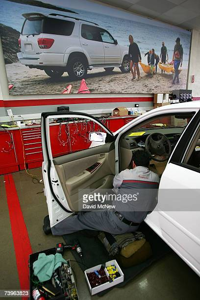 An employee installs an alarm in a new Toyota at the world's largest auto dealership Longo Toyota which enjoys continued strong sales after a record...