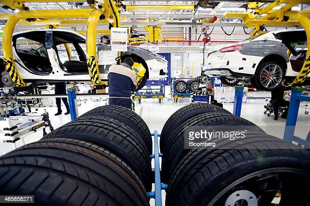 An employee installs an alloy wheel and tire on a Maserati Ghibli luxury automobile produced by Maserati SpA as it travels along the production line...