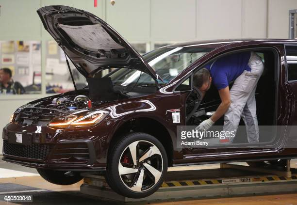 An employee installs flooring into a Golf 7 automobile at the Volkswagen factory on March 9 2017 in Wolfsburg Germany The company whose core brand...