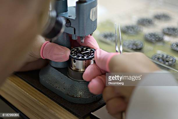 An employee installs the hands onto the dial of a Luminox P38 lightening automatic 9401 series wristwatch using a hand press at the Mondaine Watch...