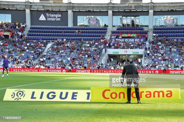 An employee installs the Ligue 1 signs at the start of the French L1 football match Toulouse against Dijon on August 17 2019 at the Municipal Stadium...