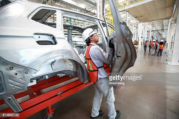 An employee installs the rear passenger door on a test frame for a Volkswagen AG Tiguan compact sport utility vehicle inside the company's new...