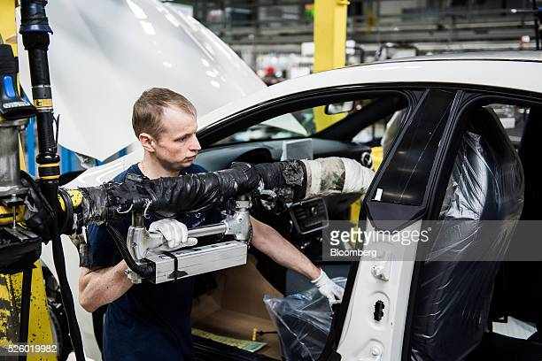 An employee installs the seats in an automobile on the production line at the Mercedes-Benz AG automobile plant, operated by Daimler AG, in...