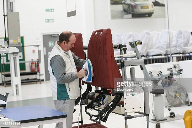 An employee irons creases from the material of seat destined for a Bentley automobile as he works in the upholstery department at the Bentley Motors...