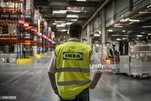 An employee is at work at a warehouse of world's largest furniture retailer Ikea on March 18 2014 in SaintQuentinFallavier AFP PHOTO / JEFF PACHOUD