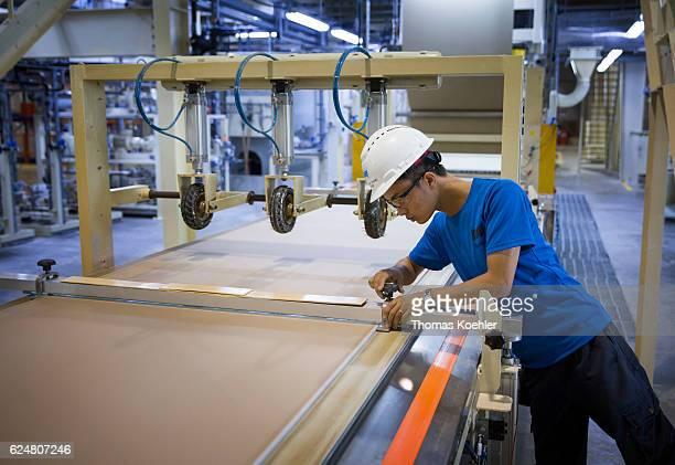 An employee is cutting gypsum boards at Knauf Vietnam Ltd on October 30 2016 in Hai Phong Vietnam