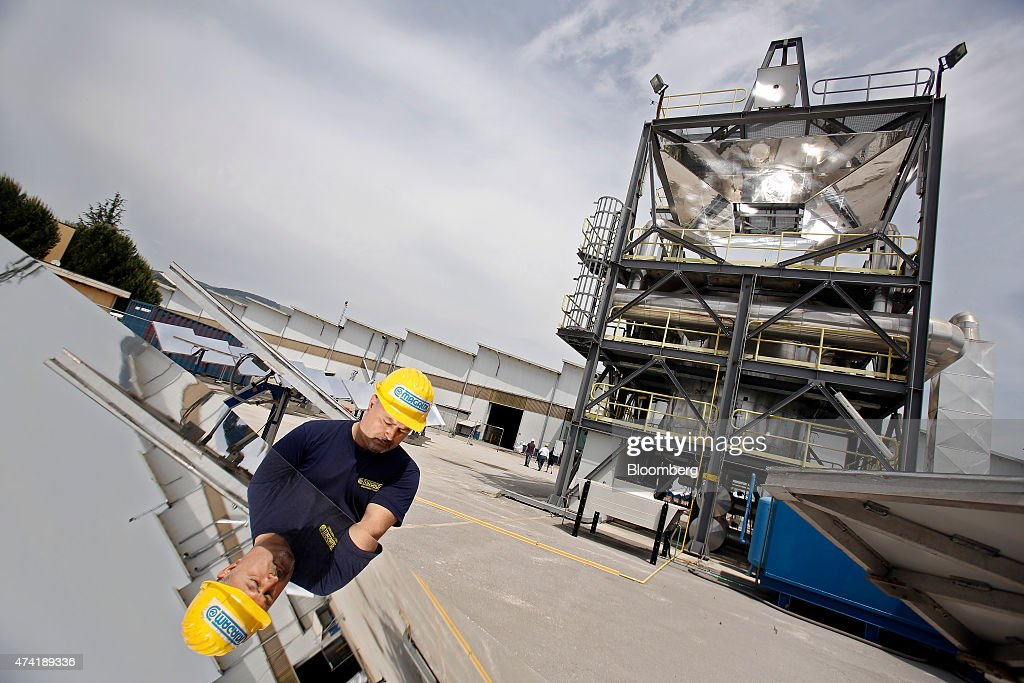 An employee is reflected in a heliostat panel as a solar generation unit stands beyond at a Solar Thermoelectric Magaldi (STEM) pilot plant, operated by Magaldi Group, in Buccino, Italy, on Monday, May 18, 2015. The project captures the energy of the sun which is transferred via the generation unit to heat retaining silica sand, producing steam that powers a turbine and is suitable for use in systems operating over a large temperature range. Photographer: Alessia Pierdomenico/Bloomberg via Getty Images