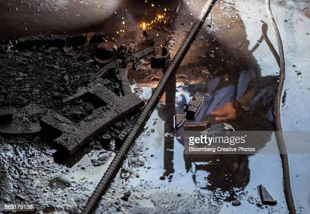 an employee is reflected in water while working next to an electric arc furnace - electric arc furnace stock photos and pictures