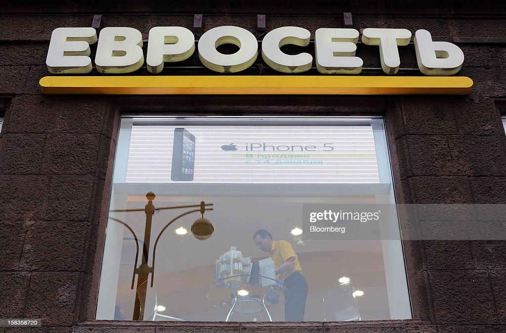 An employee is seen at work through the window of a Euroset Holding NV mobile phone store in Moscow, Russia, on Thursday, Dec. 13, 2012. OAO MegaFon and its main shareholder billionaire Alisher Usmanov bought 50 percent of Euroset Holding NV in a deal that gives Russia's biggest handset retailer an enterprise value of $2.3 billion. Photographer: Andrey Rudakov/Bloomberg via Getty Images