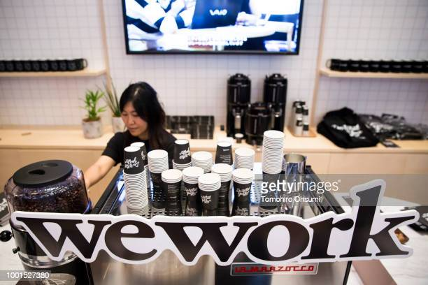 An employee is seen behing the logo of WeWork Companies Inc during the SoftBank World 2018 conference on July 19 2018 in Tokyo Japan The annual...