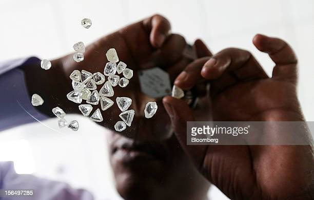 An employee is seen from below using a magnifier to inspect a selection of uncut diamonds in this arranged photograph at DTC Botswana a unit of De...
