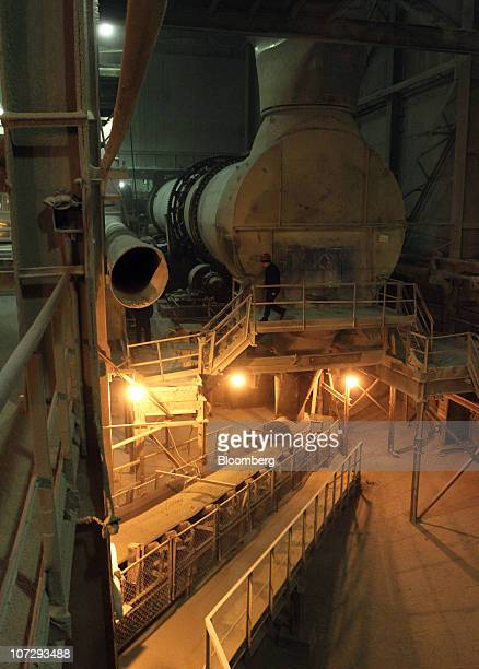An employee is seen near a conveyor moving OAO Ammophos phosphate plant fertilizer at the OAO PhosAgro plant in Cherepovets Russia on Thursday Dec 2...