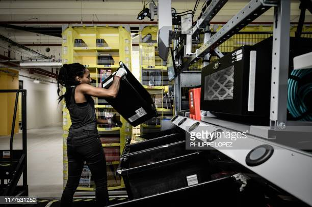 An employee is seen on duty at work stations part of mobile robotic fulfilment systems also known as 'Amazon robotics' during the inauguration of a...