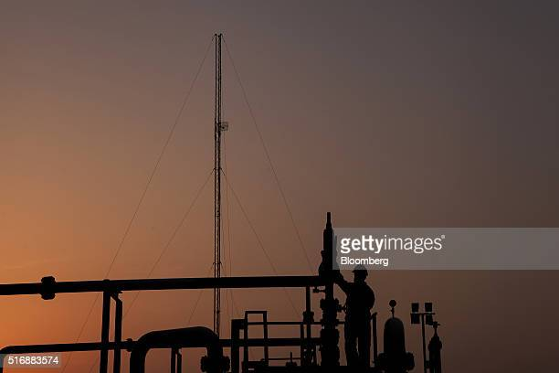 An employee is silhouetted as he works at sunset at the Mari Petroleum Co plant in Daharki Sindh Pakistan on Thursday March 17 2016 New additional...