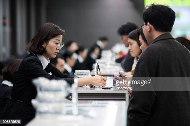 An employee left assists passengers at a Korean Air Lines Co checkin counter inside the terminal 2 building at Incheon International Airport in...