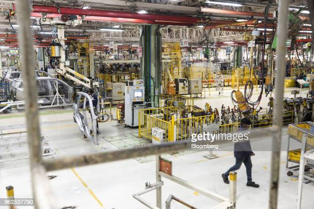 An employee left carries a door plate for a Mahindra Mahindra Ltd XUV 500 sportutility vehicle on the production line at the company's facility in...