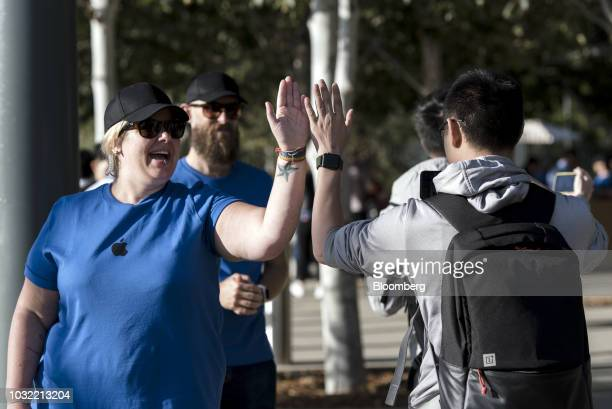 An employee left highfives an attendee arriving ahead of an Apple Inc event at the Steve Jobs Theater in Cupertino California US on Wednesday Sept 12...