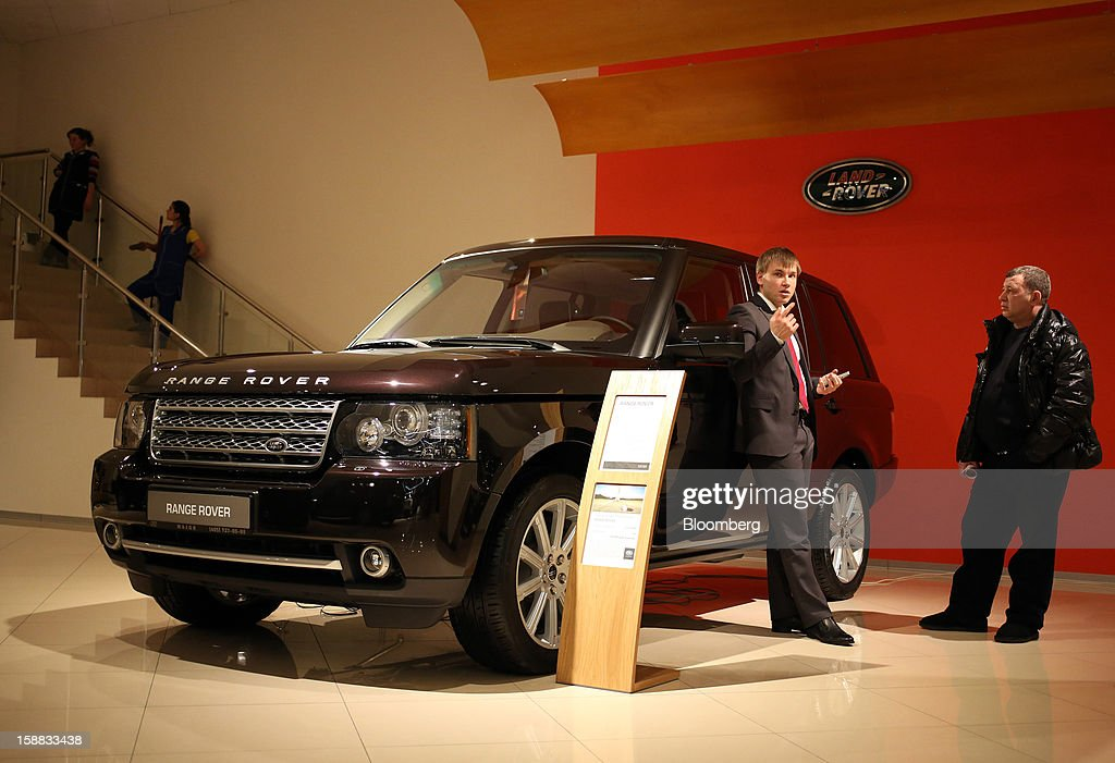 An employee, left, leans against a new Range Rover automobile while speaking to a customer, right, in a Jaguar Land Rover auto dealership in Moscow, Russia, on Thursday, Dec. 27, 2012. Tata Motors Ltd.'s Jaguar Land Rover luxury unit signed a letter of intent with Saudi Arabia's government to study the feasibility of setting up a factory to build its models locally. Photographer: Andrey Rudakov/Bloomberg via Getty Images