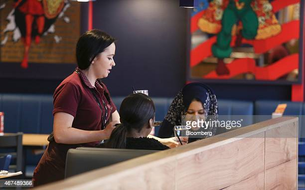 An employee left serves customers drinks at their table inside a Pizza Hut restaurant owned by Yum Brands Inc at the company's flagship restaurant on...