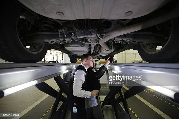 An employee left shows a customer the underside mechanics of a Toyota Rav 4 raised on an hydraulic lift in the 'acceptance zone' of a Toyota Motor...