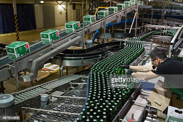An employee lifts bottles of Heineken beer from the production line at the Heineken NV brewery in Saint Petersburg Russia on Wednesday Nov 18 2015...