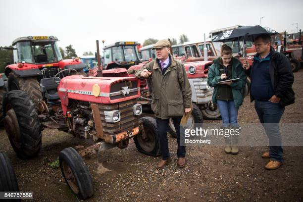 An employee listens to bids from potential buyers of a tractor manufactured by Massey Ferguson Corp at the Cheffins Cambridge Machinery Sales monthly...