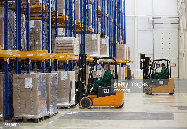 An employee loads a pallet of pharmaceuticals into a storage bay using a forklift truck at OAO Pharmstandard's Leksredstva drug manufacturing unit in...