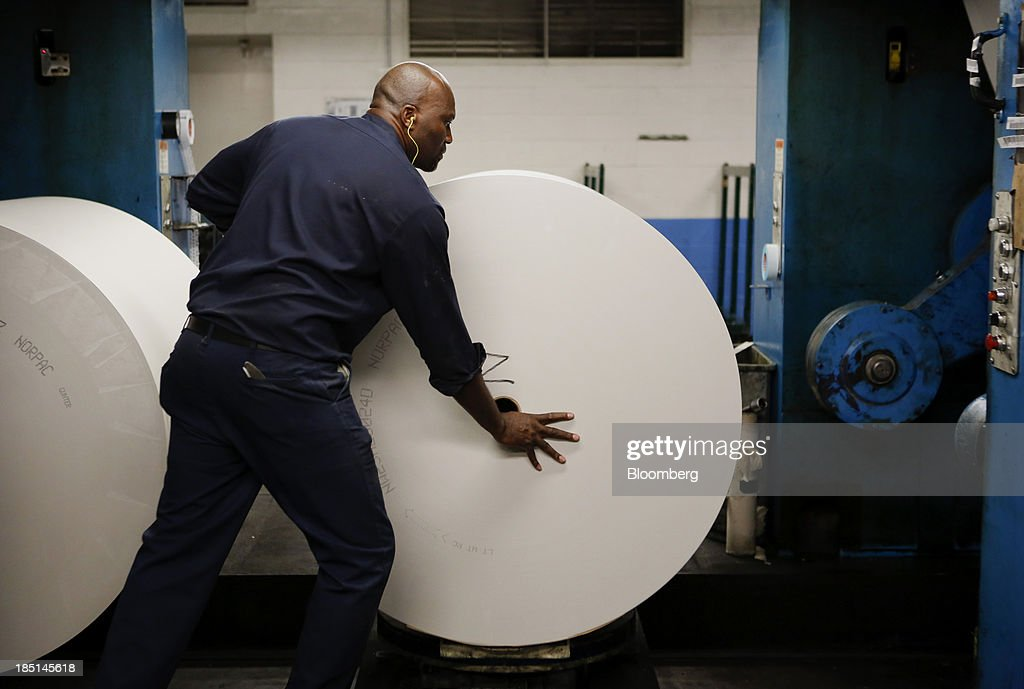 An employee loads a roll of newsprint at the Los Angeles Times Olympic Press facility in Los Angeles, California, U.S, on Wednesday, Oct. 16, 2013. Congress ended the 16-day government shutdown, raising the U.S. debt limit after the leaders of the Senate reached a bipartisan agreement to end the nation's fiscal impasse. Photographer: Patrick T. Fallon/Bloomberg via Getty Images