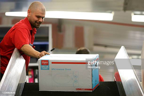 An employee loads an Argosbranded microwave onto a conveyor belt inside the warehouse at an Argos store operated by Home Retail Group Plc in Enfield...