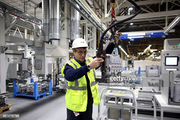 An employee loads an engine component into a coordinated measuring machine in the yettobecompleted engine production line at a Ford factory on...
