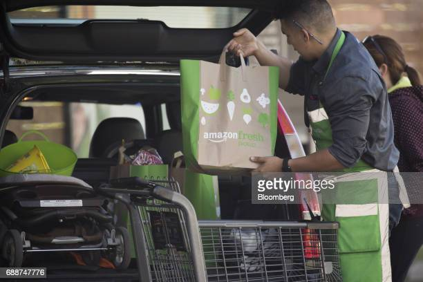 An employee loads bags of groceries into a customer's vehicle at an AmazonFresh Pickup location in Seattle Washington US on Friday May 26 2017...