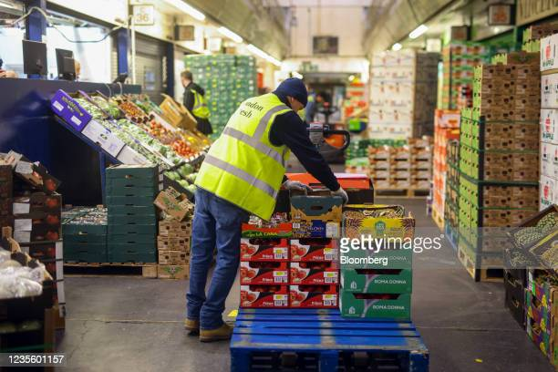 An employee loads boxes of fresh fruit on to a pallet in the Buyers Walk at New Covent Garden Market wholesale market in London, U.K., on Thursday,...