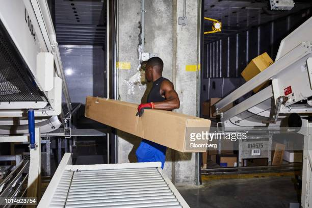 An employee loads packages on a delivery truck at the FedEx Corp Ground distribution center in Jersey City New Jersey US on Tuesday Aug 7 2018 FedEx...