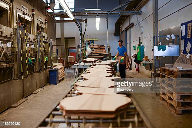 An employee loads precut wood sheets onto a conveyor belt during manufacture at the Fritz Hansen A/S furniture company's assembly plant in Lynge...