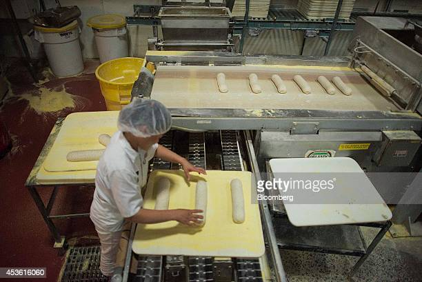 An employee loads trays of dough onto a conveyor belt to move towards the oven at the Orlando Baking Co in Cleveland Ohio US on Wednesday Aug 13 2014...