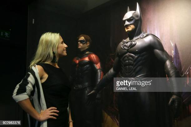 An employee looks at a costume of Batman worn by George Clooney in Batman and Robin designed by Bob Ringwood and Robert Turturice during a press...