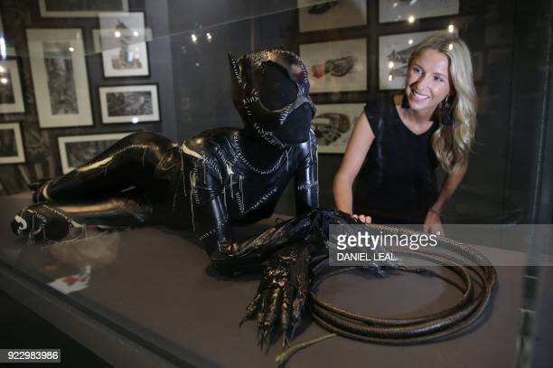 An employee looks at a costume worn by US actress Michelle Pfeiffer in the movie 'Batman Returns during a press preview of 'DC Comics Exhibition Dawn...