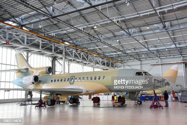 An employee looks at a Dassault Aviation's Falcon 8X sitting on an assembly line in Merignac southwestern France on January 14 2019 French Defence...