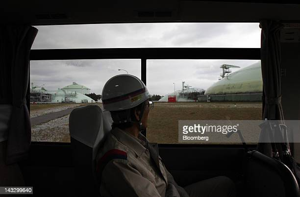 An employee looks at a liquefied natural gas tank from a bus window at Tokyo Gas Co's Sodegaura plant in Sodegaura City Chiba Prefecture Japan on...
