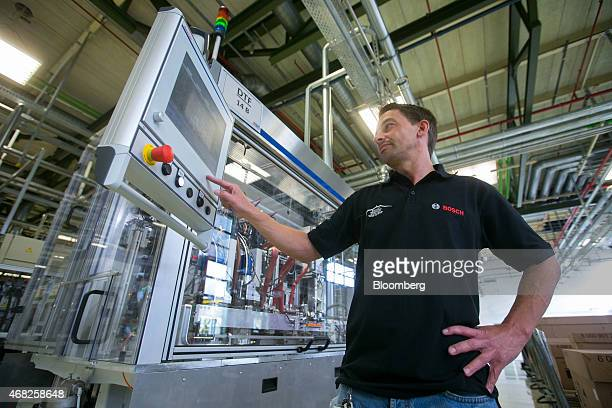 An employee looks at a monitor on the automobile gasoline direct injector valve assembly line at the Robert Bosch GmbH plant in Blaichach Germany on...
