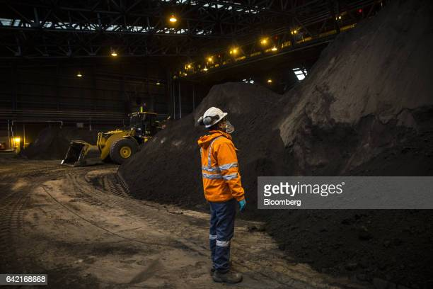 An employee looks at a pile of copper concentrate at a warehouse in the Ferrobamba pit one of the three pits that will be mined by MMG Ltd's Las...