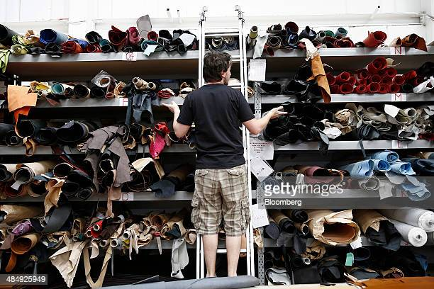 An employee looks at a storage rack of materials to be used for GlobeTrotter goods at GlobeTrotter Suit Case Company Ltd's workshop in Hoddesdon UK...