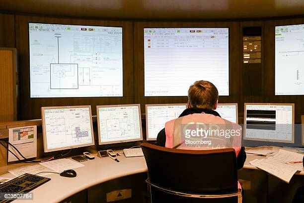 An employee looks at operational information displayed on computer monitors inside the control room at the Evolutionary Power Reactor nuclear power...