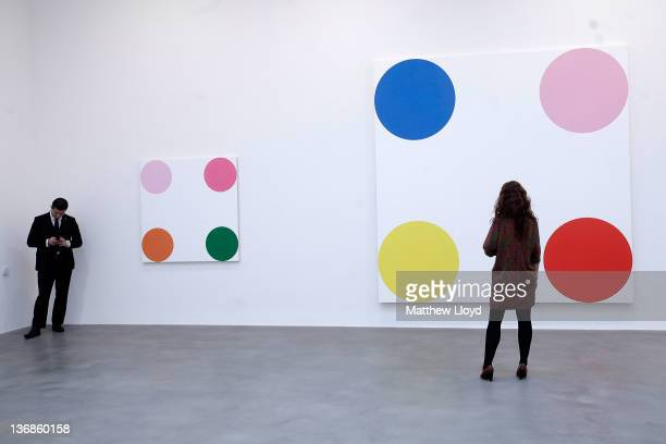 An employee looks at the artwork 4Chlorephenol 2008 part of the artist Damien Hirst's exhibition The Complete Spot Paintings at the Gagosian Gallery...