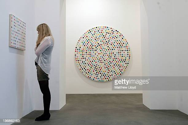 An employee looks at the artwork Hydroquinone 2006 part of the artist Damien Hirst's exhibition The Complete Spot Paintings at the Gagosian Gallery...
