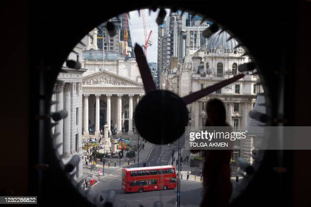 An employee looks at the view of London's business centre from a window at the WeWork, coworking and office space in the City of London, on April 13...